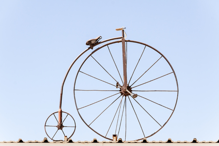 Side view of penny farthing against a blue sky. photo