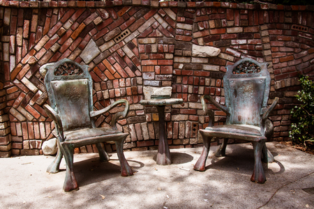 bronzed: A pair of metal chairs and a side table outdoors in a park. Stock Photo