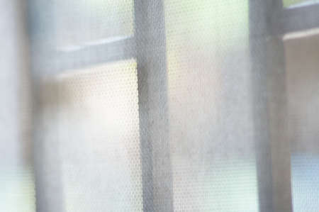 Mosquito nets on window blur as backdrop