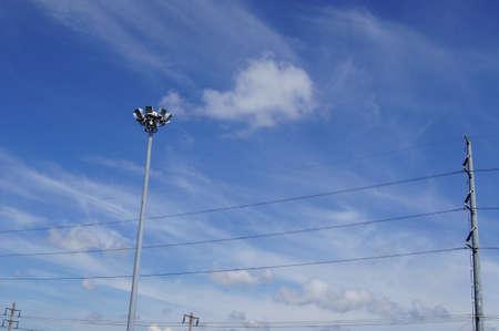 Street light pole ang electric line against blue sky