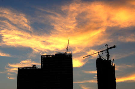 Silhouette buildings under construction against a golden sky in the evening photo
