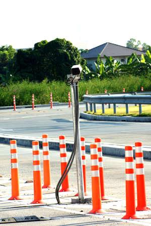 bollards: Security camera with orange bollards Stock Photo