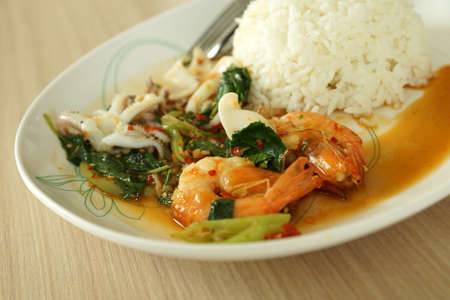 serv: Thai fried Shrimp and squid in basil sauce serv with jasmin steam rice call as Pad Kaprao Tale in Thai name