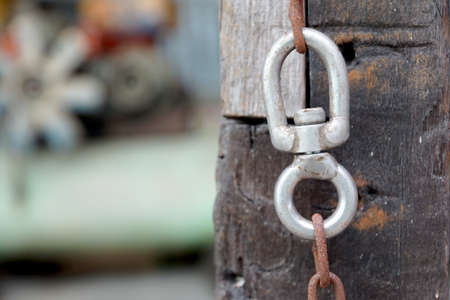 Hanging rusty chain and metal ring on wood pillar