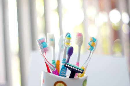 Colorful toothbrushes and razor in a cup for family use photo