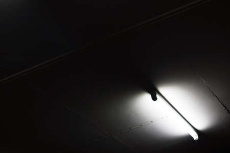 Fluorescent tube on the ceiling of dark room for abstract background photo