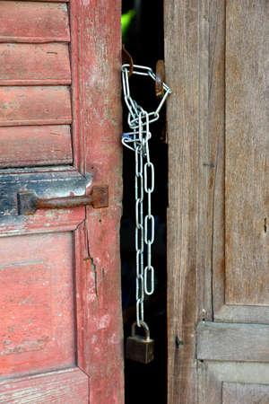 splintered: Old wood door locked with chain and padlock
