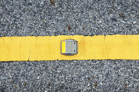 Road stud with yellow reflector on the yellow line of asphalt road