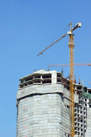 Contruction building with crane against blue sky photo