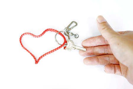 Hand holding a key with Red strap Heart-Shaped isolated on white background photo