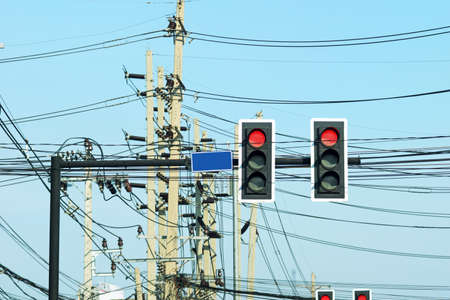 Traffic light poles and power poles with tangled wires on the traffic intersection -Bangkok, Thailand  photo