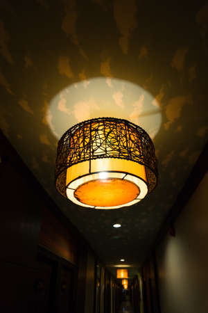 A round shaped vintage lamp on the ceiling in the dark photo