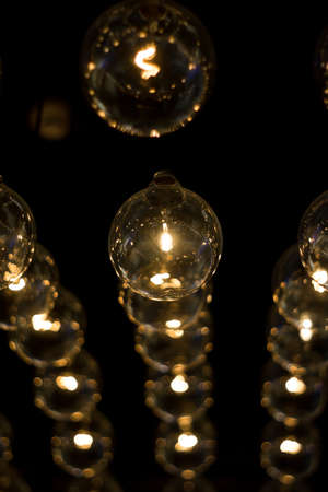 electric lamps hanging on the ceiling in the dark room Stock Photo