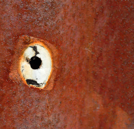 Close up of a hole on rusty metal sheet surface
