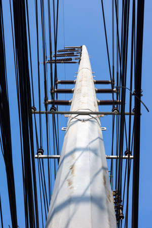 Electric pole with wires under blue sky