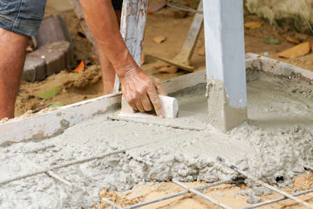 concrete surface finishing: Construction worker using trowel to finish wet concrete floor Stock Photo