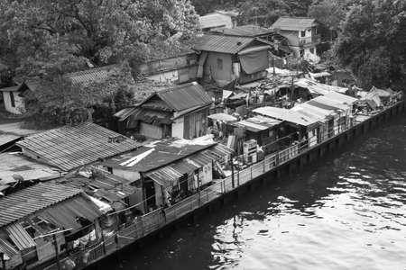 encroaching: Urban ghetto house village canal side , Bangkok Thailand.  - Black and White