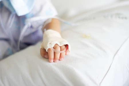 Saline intravenous (iv) drip in a Childrens patient hand