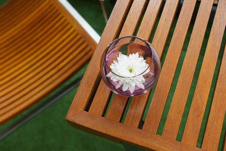Decorative little flower in a glass on wooden slats table in the restaurant