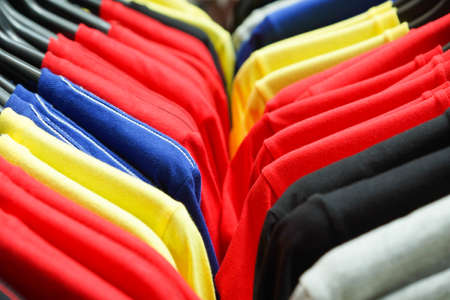 Cloth Hangers with Colorful T-Shirts as abstract background