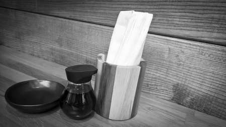 Tissue paper in wooden box with sauce bottle on wooden table in the restaurant - Black and White Stock Photo