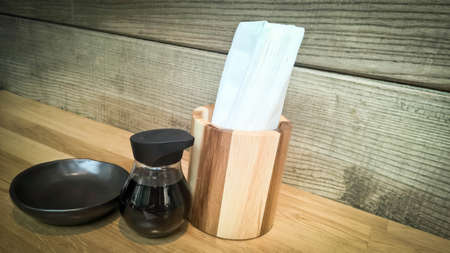 Tissue paper in wooden box with sauce bottle on wooden table in the restaurant Stock Photo