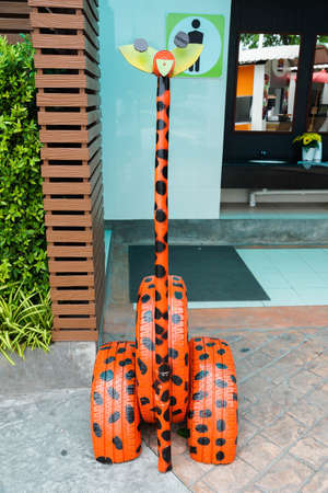 Decorative giraffe made by old tires and recycled materials - Outdoor decoration - toilet - Men restroom sign Stock fotó