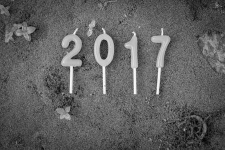 new year 2017 (A.D.) candle text on green moss background - Black and White Stock Photo