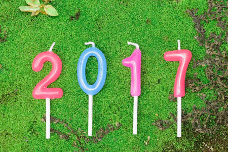 new year 2017 (A.D.) candle text on green moss background Stock Photo