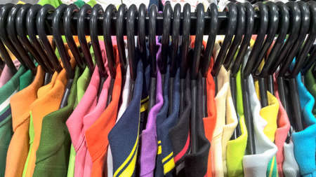 Close-up of colorful t-shirts hanging in clothes store Stok Fotoğraf