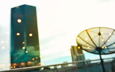 Abstract Blurred background of urban scene - Building rooftop and satellite with bokeh and warm light shining