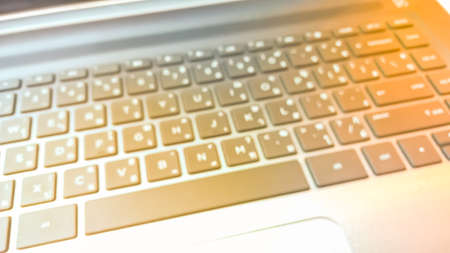 english letters: Blurry keyboard with warm light shining as abstract background - Business and Technology Concept
