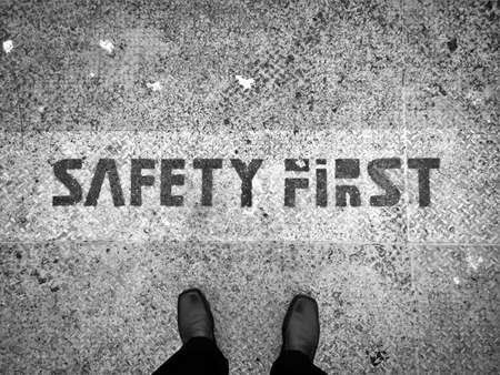 Man stand on rusty grunge metal floor with safety first word as concept background - Black and White
