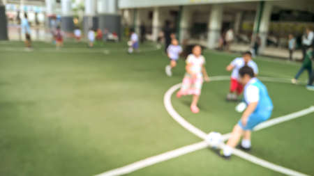 Blurry scene of children play soccer in football field at school - Education concept background
