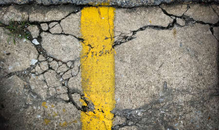 Old damaged street surface with yellow line as background