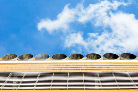 Exhaust vents of industrial air conditioning and ventilation units on the roof top of large building