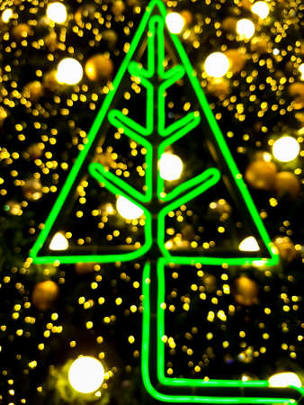 Blurred background of Christmas decoration with green LED Pine tree and golden bokeh lights