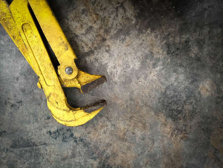 Old Yellow Industrial Clamp lay on grunge concrete floor background with copy space