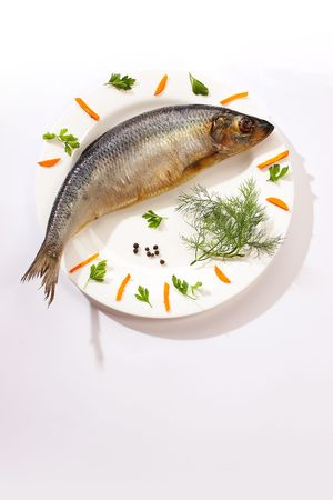 herring on the white plate with black pepper and carrot