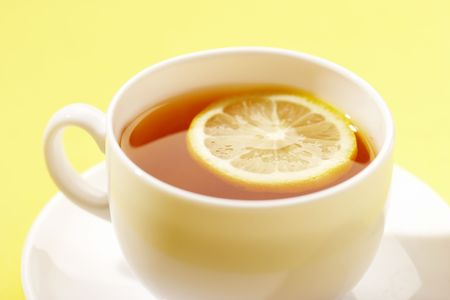 cup of tea with lemon over yellow Stock Photo