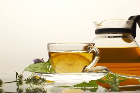 Tea pot with cup and leaves of mint and lemon-balm photo