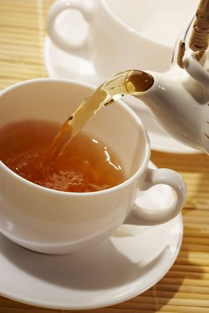 flowing golden tea into cup photo