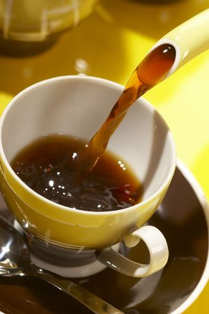 Pouring black coffee into coffee cup