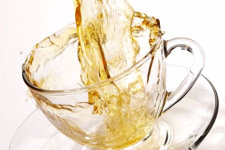 Pouring tea into glassy tea cup photo