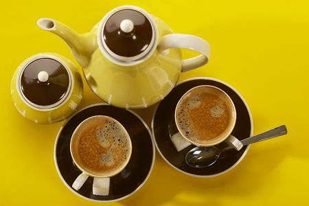 coffee-pot and two cup of coffee over yellow photo