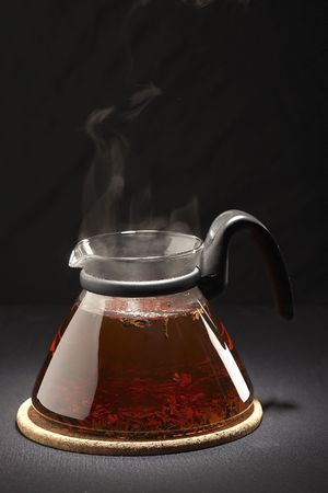 glassy teapot with hot tea over black background