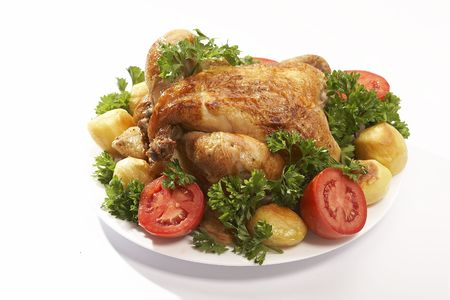 roasted chicken with vegetables and parsley on the plate