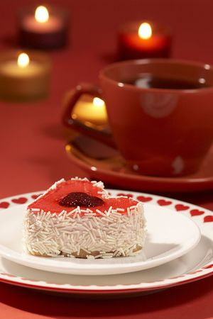 red romantic still life with tart and candle over red photo
