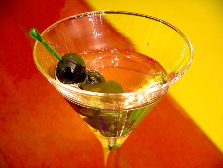 cutglass: alcohol cocktail with olives in the special glass under neon lights Stock Photo