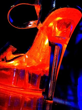 woman strip tease shoe under special neon light at night club